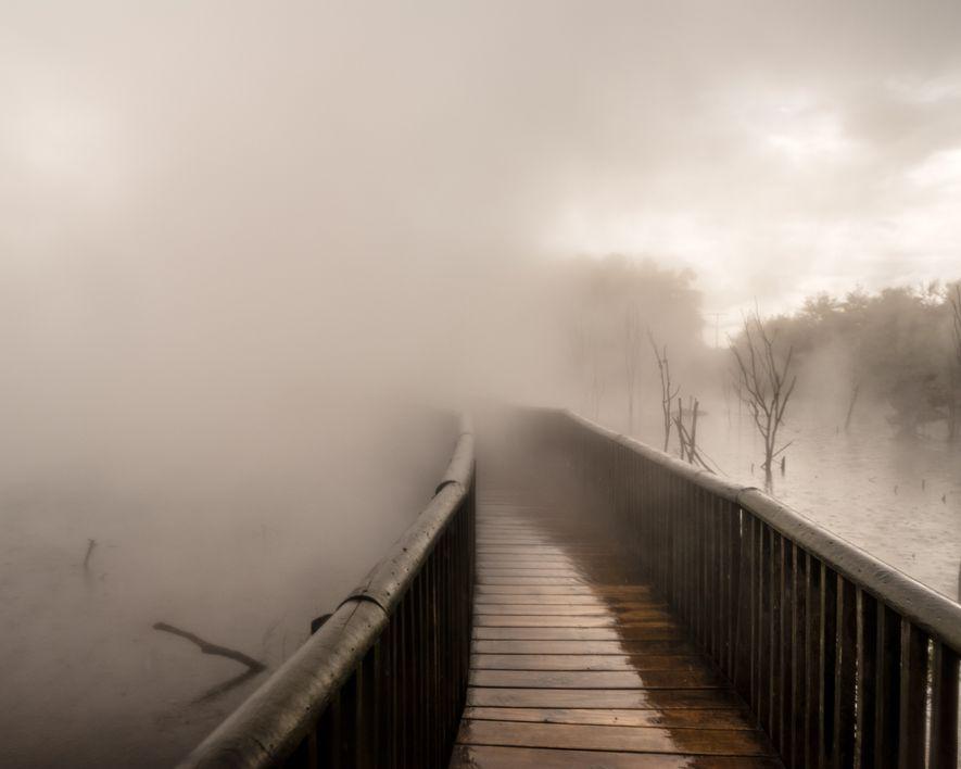 Vapor de atividade geotermal encobre uma passarela no Parque Kuirau, Rotorua.