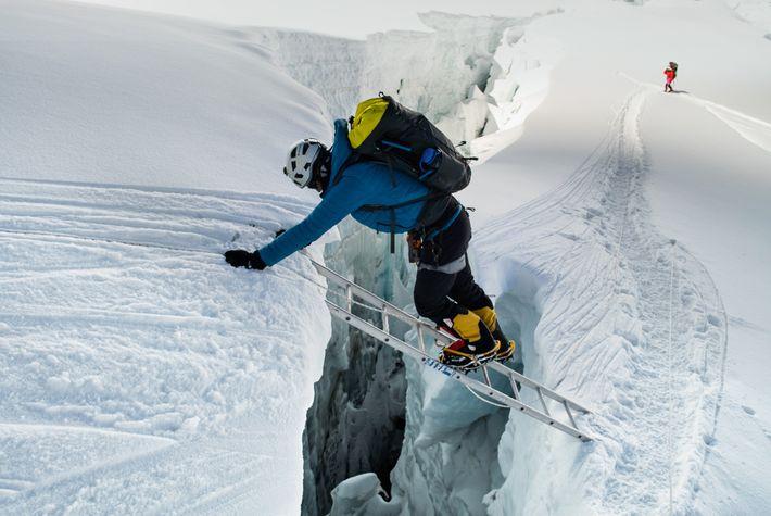 Roman atravessa uma fenda da Cascata de Gelo de Khumbu, com a ajuda de uma escada. ...