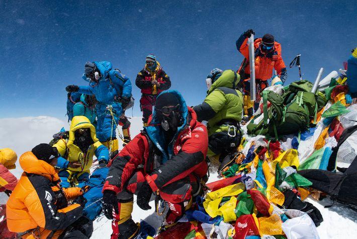 Roman (no centro, de vermelho e máscara de oxigênio) descansa no cume do Everest. Para o ...