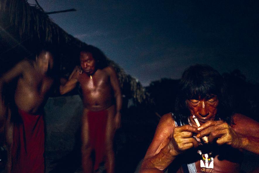 O cacique Piriri fuma seu charuto enquanto outros wajãpis celebram com cantos tradicionais. Nessas festas, eles costumam consumir caxiri, uma bebida típica com forte teor alcóolico preparada da fermentação da mandioca.