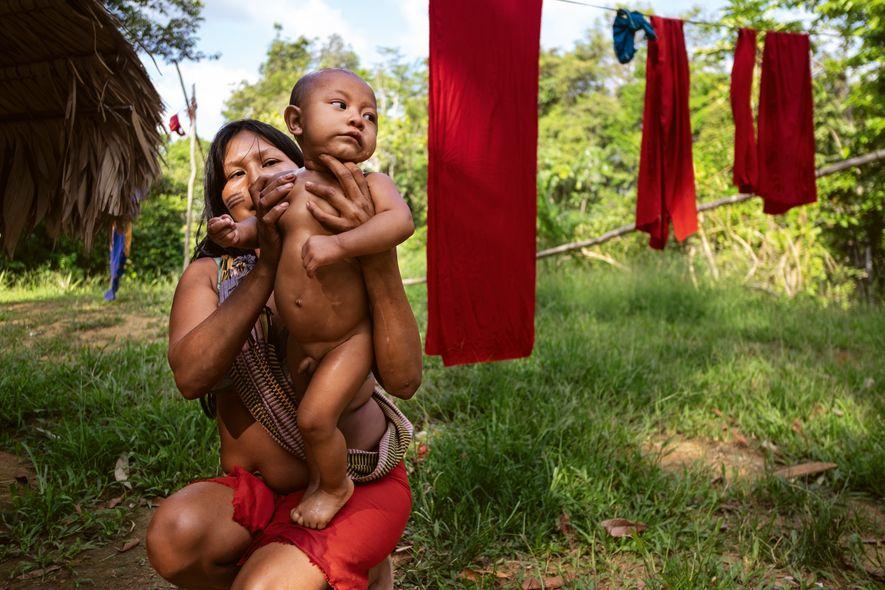 Uma wajãpi banha seu bebê ao lado dos panos típicos que secam. O tecido vermelho, tingido de urucum, é uma marca do povo indígena.