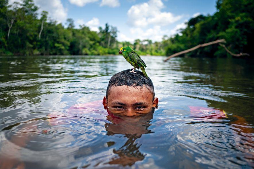 Um morador da Reserva de Desenvolvimento Sustentável do Rio Iratapuru toma banho no Rio Jari com seu papagaio. Vizinhos da Terra Indígena Waiãpi, os moradores da RDS se tornaram aliados dos indígenas no combate e fiscalização do território contra a ameaça de garimpeiros.