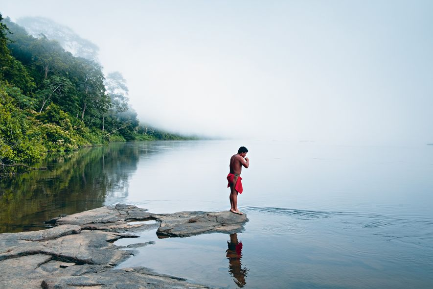 Masakão escova os dentes às margens do Rio Mukuru no amanhecer. Na cultura wajãpi, cada elemento da natureza – como as pedras e os rios – possui espíritos protetores. Pirajarã é o guardião dos peixes e Kajajara é o grande defensor das florestas.