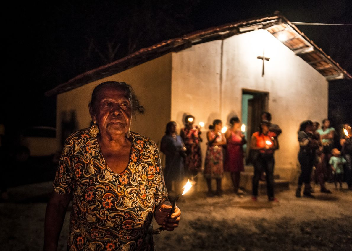 Mulher quilombola acende uma vela em comunidade Kalunga