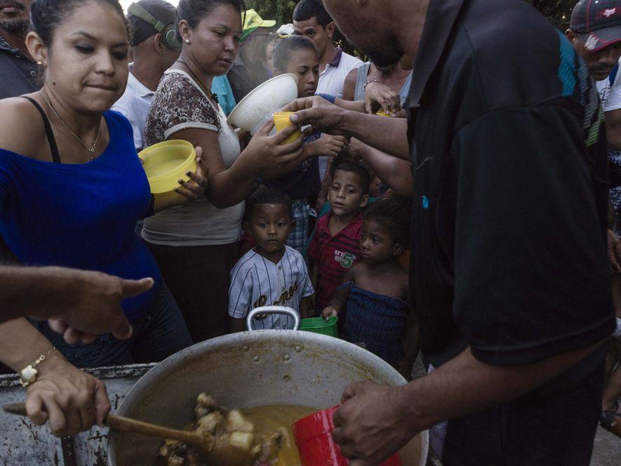 Longa filas se formam na Praça Simón Bolívar para ganhar a comida doada por voluntários e ...
