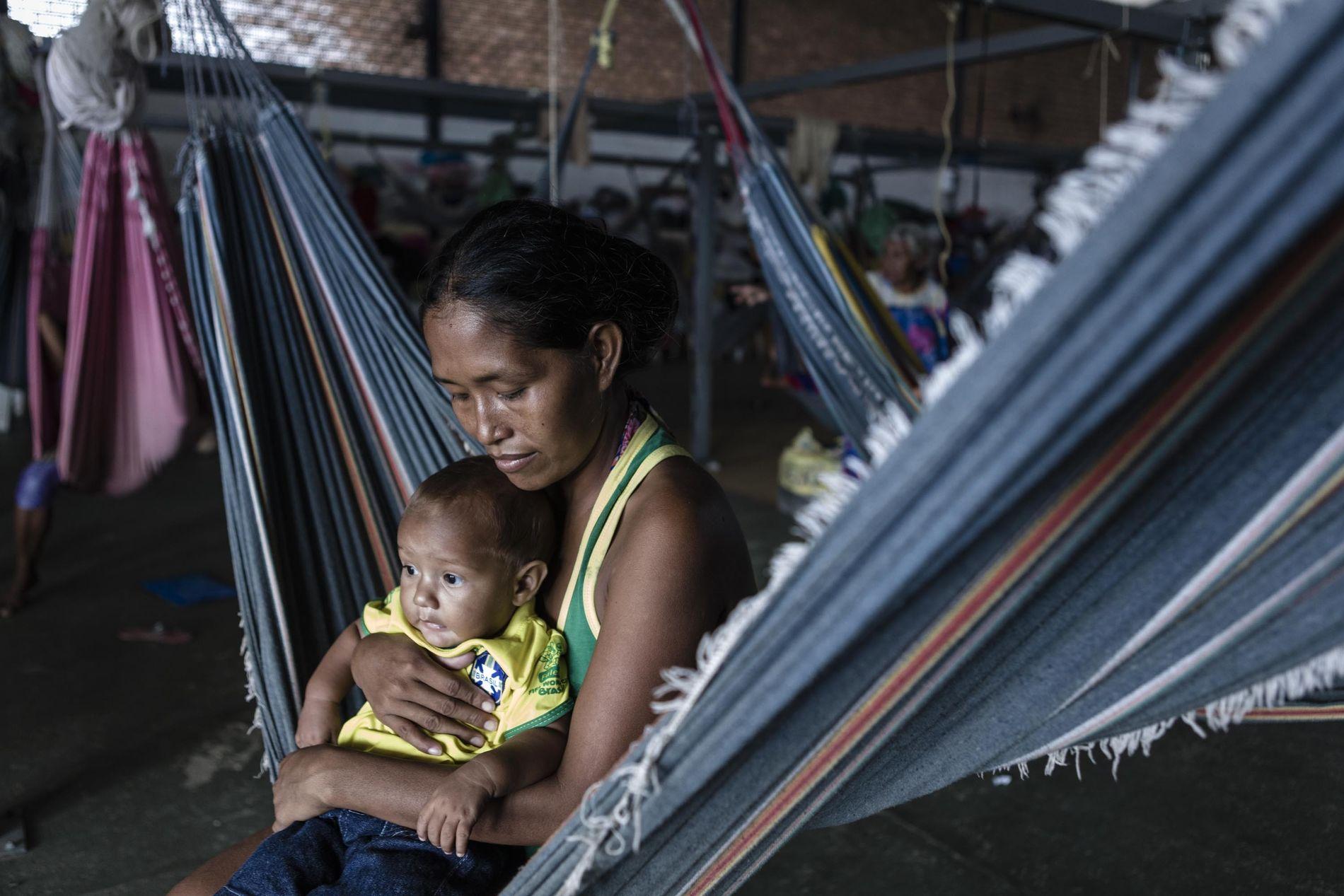 No abrigo de Pacaraima, uma mãe do povo Warao segura o seu filho. Apesar de não ...