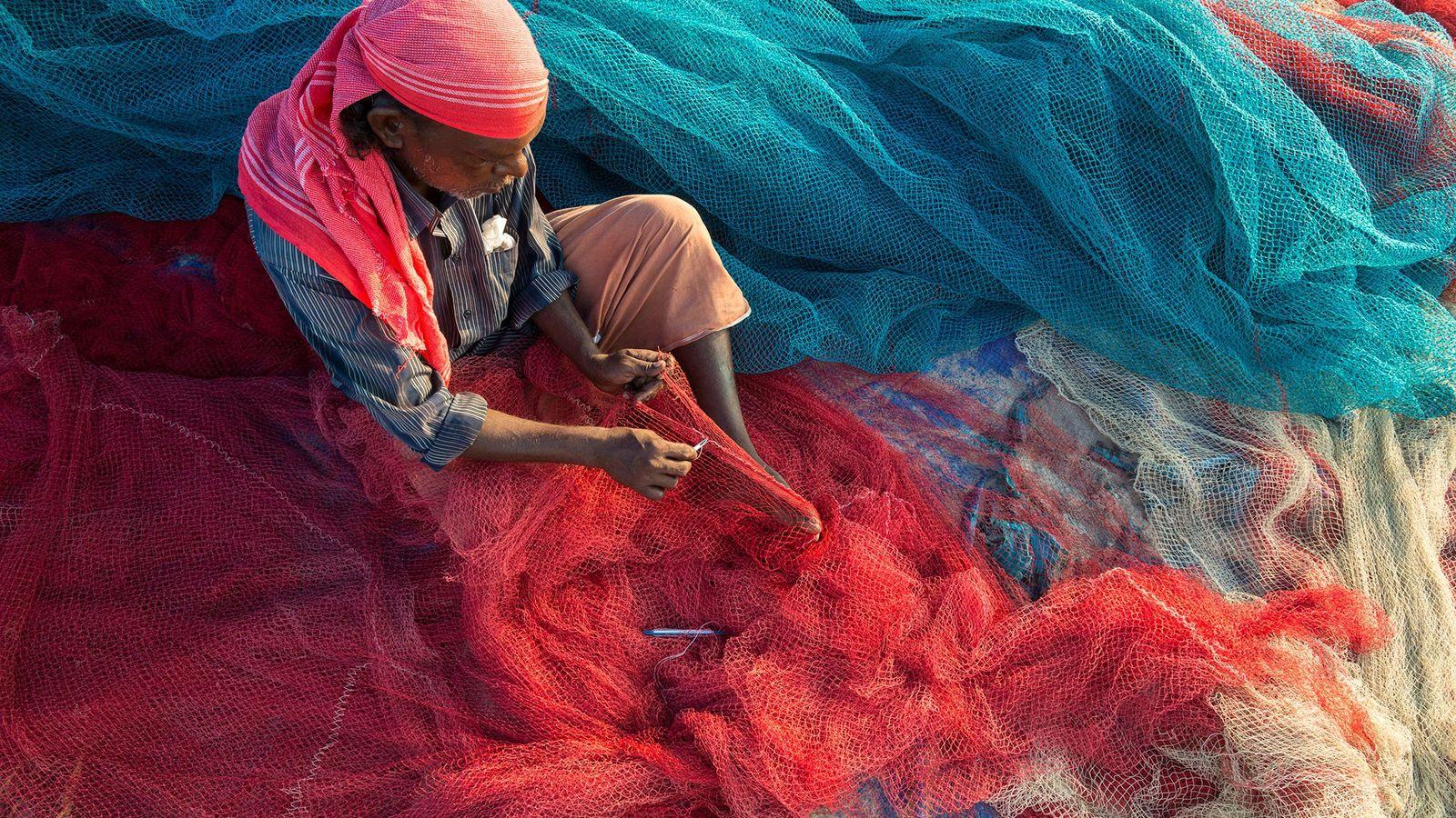 Um pescador em Kerala, Índia, conserta redes na praia. A poluição plástica pode danificar obstruir as ...