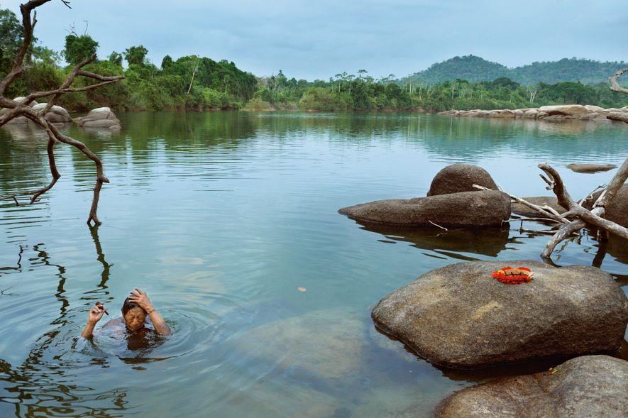 Deixando o cocar e os óculos sobre uma pedra, o chefe Pukatire imerge no rio Iriri ...