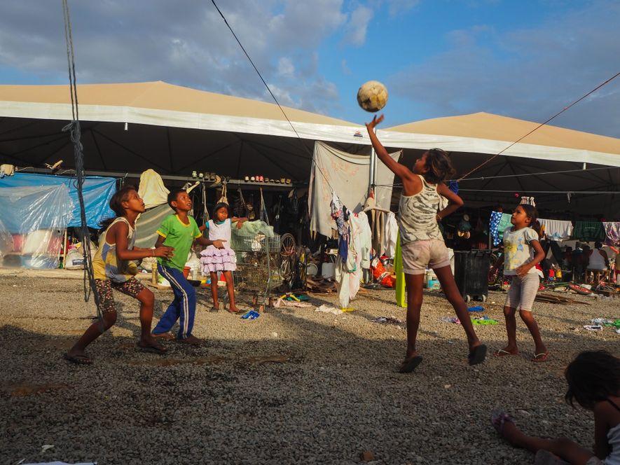 Crianças jogam vôlei com uma rede improvisada em abrigo temporário em Boa Vista, Roraima.