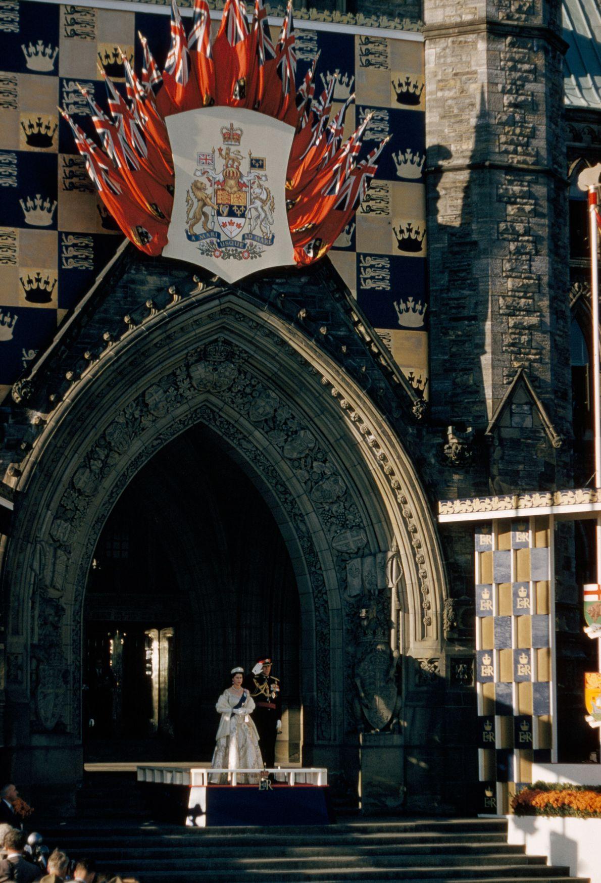 Sob um arco de arquitetura gótica, a rainha Elizabeth e o príncipe Philip participam de cerimônia e ...