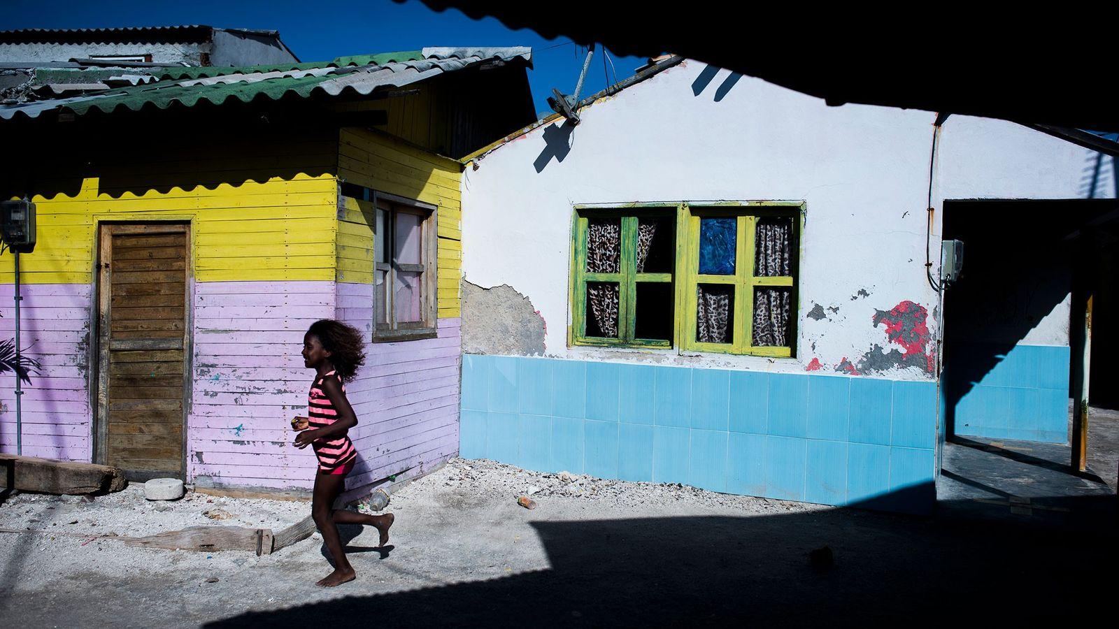Menina corre pelas casas coloridas da ilha mais densamente povoada do mundo, Santa Cruz Del Islote, ...
