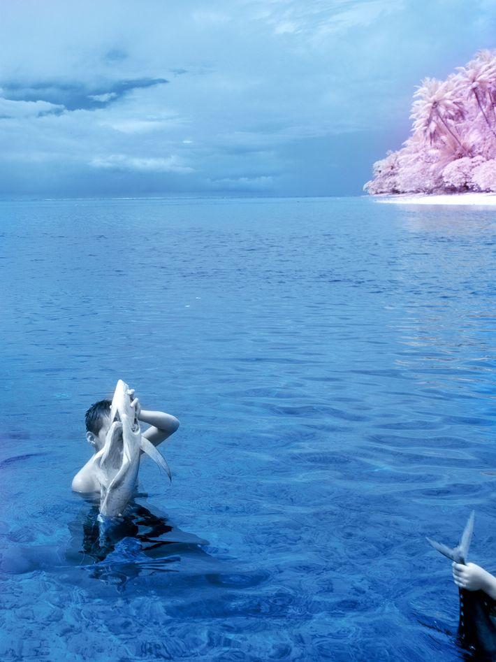 Dois meninos seguem para a costa com suas capturas, segurando o peixe fora da água para ...