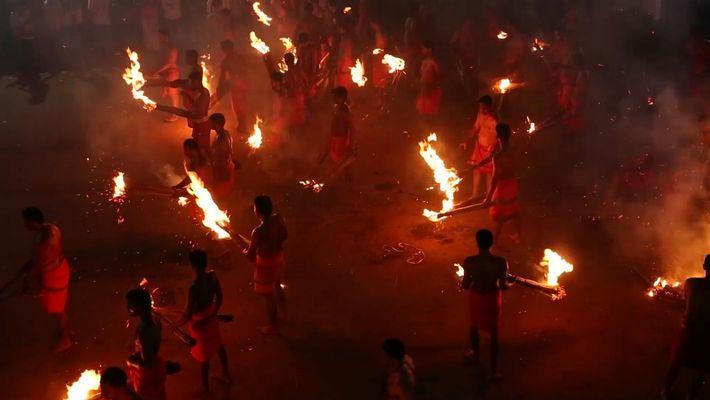 Foliões deste festival hindu lançam chamas uns nos outros