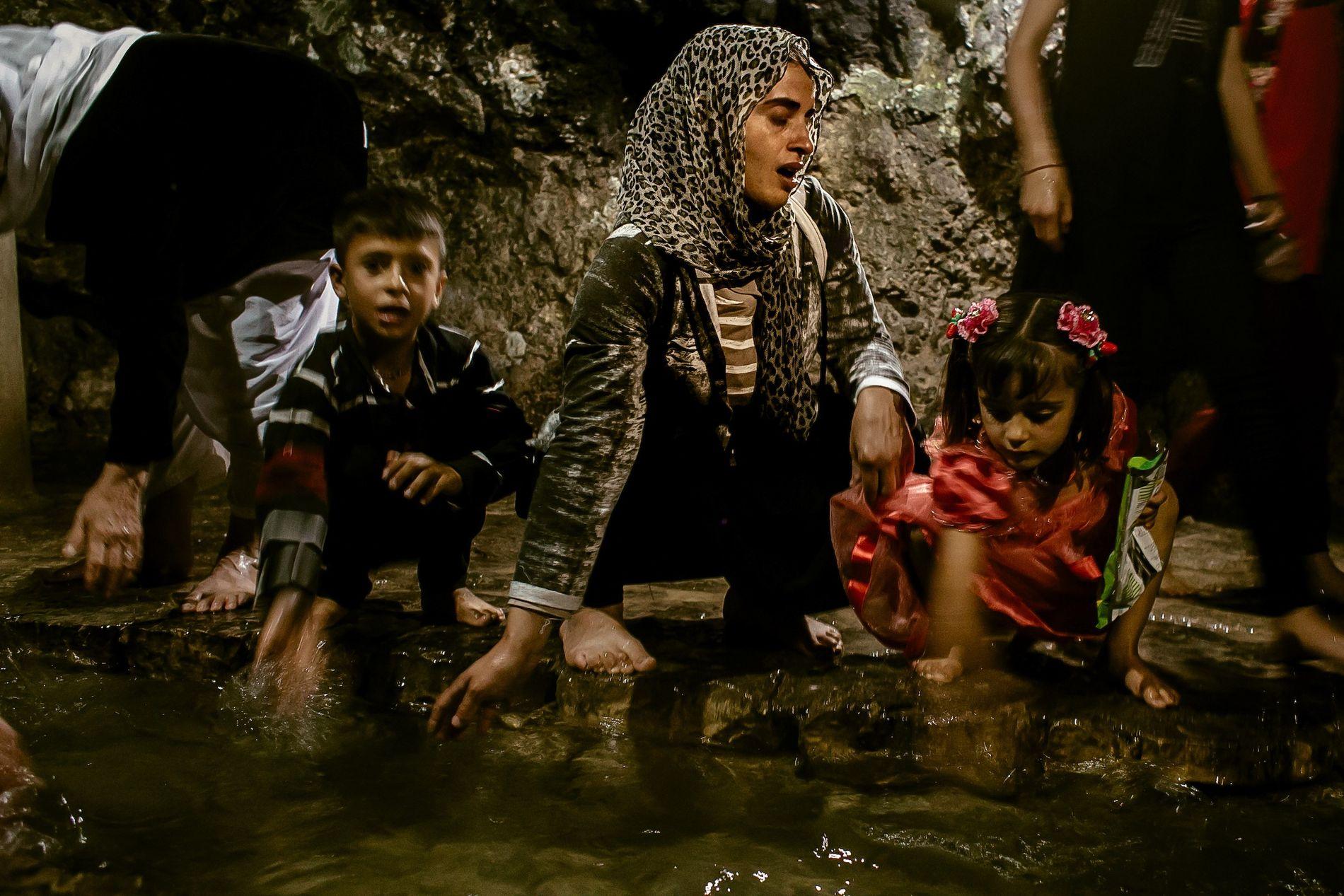 Na fonte sagrada Zamzam, no Iraque, Turkia Hussein (no centro), acompanhada de seus dois filhos, torna-se ...