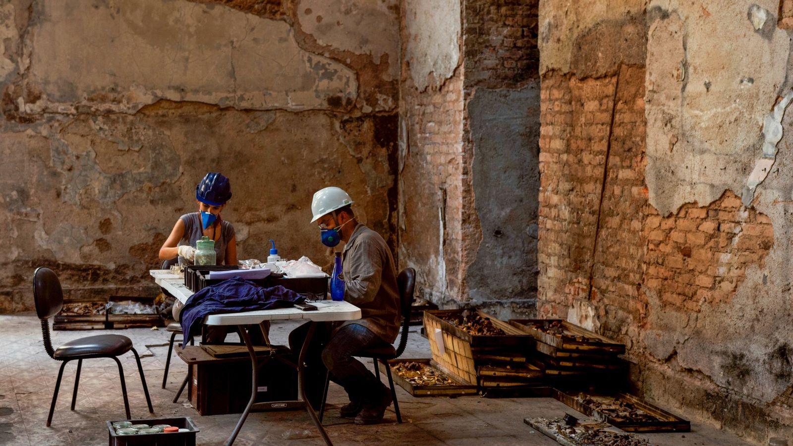 Funcionários do Museu Nacional catalogam itens do acervo recuperados no meio dos escombros do Museu Nacional.