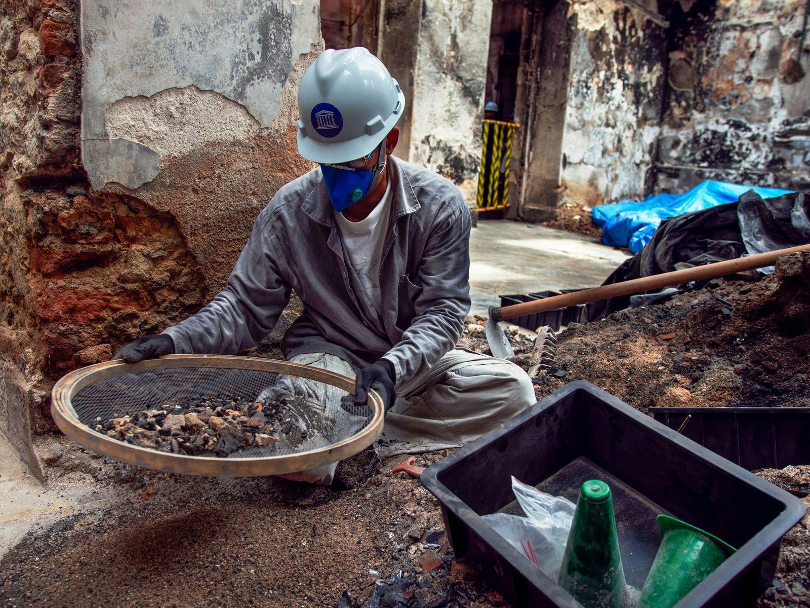 Com uma peneira, funcionário do Museu Nacional tenta separar itens do acervo de escombros do Museu ...