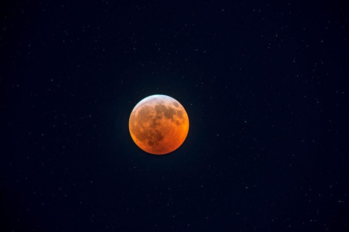 Um eclipse lunar total reluz em tons vermelhos sobre a cidade de Boston na noite de ...