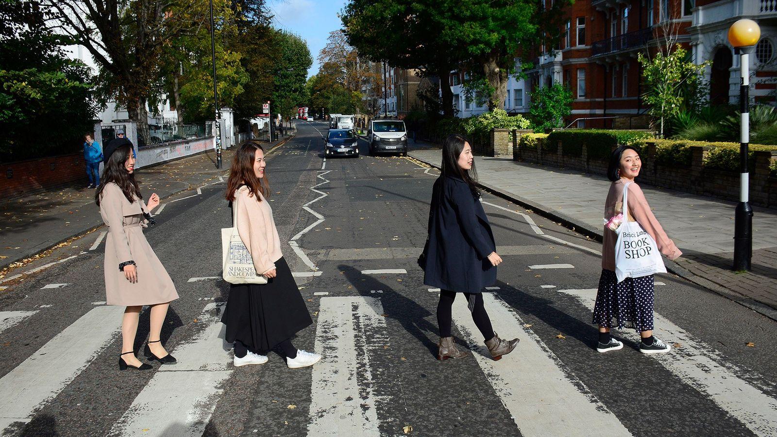Turistas posam para uma foto na icônica faixa de pedestres, próxima ao Abbey Road Studios.