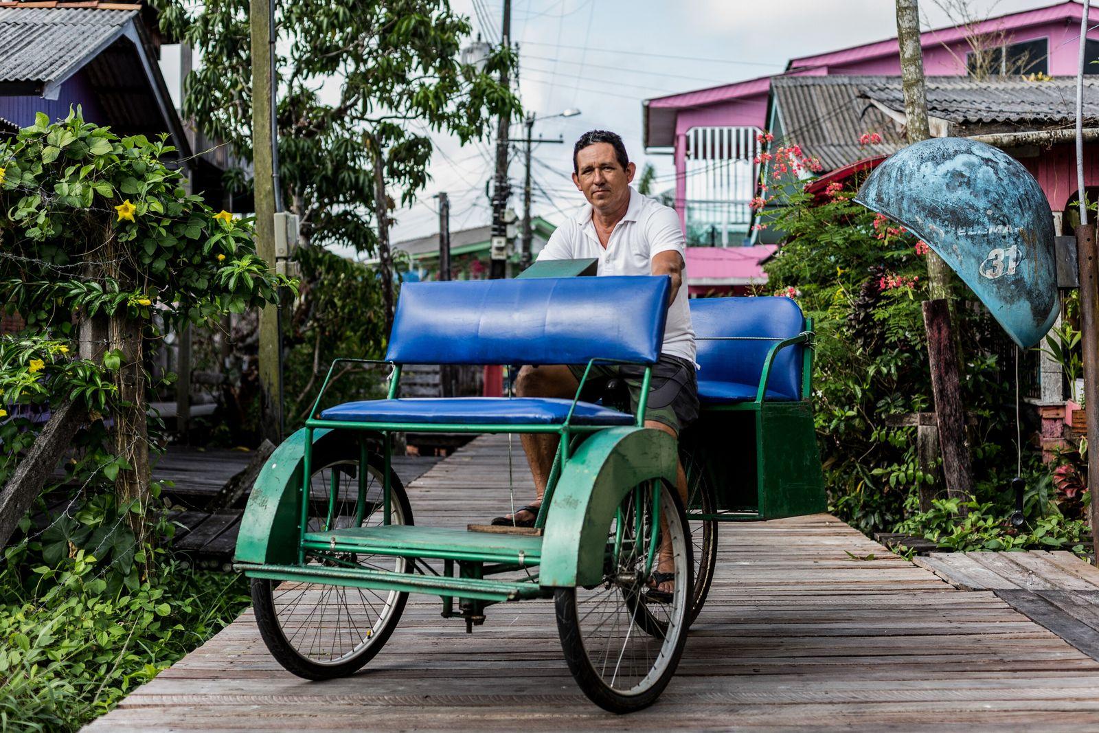 homem posa para foto em bicicleta com três rodas e quatro lugares sobre uma via de ...