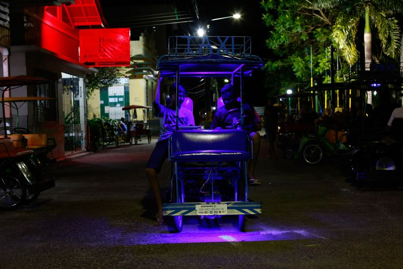 duas pessoas em uma bicicleta de quatro rodas com luzes de led roxa durante a noite