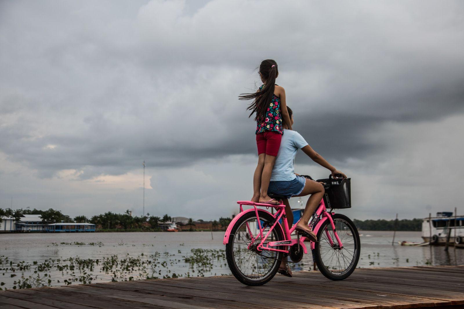 Criança viaja em pé na garupa, segurando os ombros de quem pedala – uma cena recorrente ...