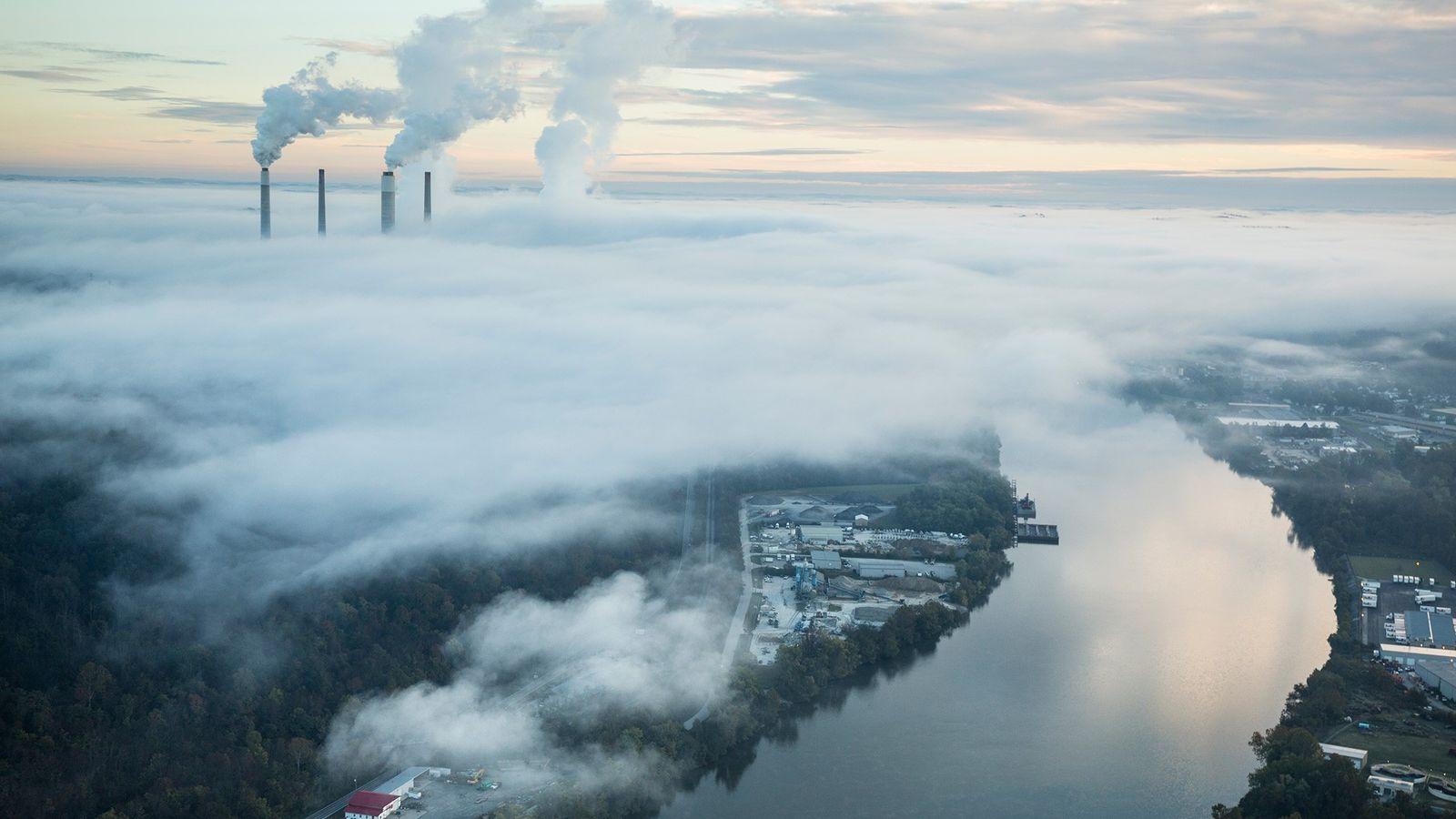 Vapor e fumaça saem das chaminés e torres de resfriamento de uma usina de energia. A ...