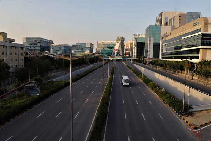 Ônibus passa sozinho por uma rodovia que geralmente fica lotada nos arredores de Nova Délhi, na ...