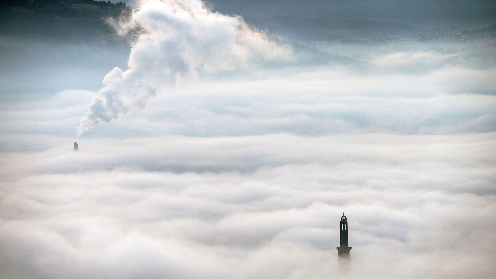 A fumaça da central de aquecimento urbano ultrapassa as nuvens próximo de uma torre de observação ...