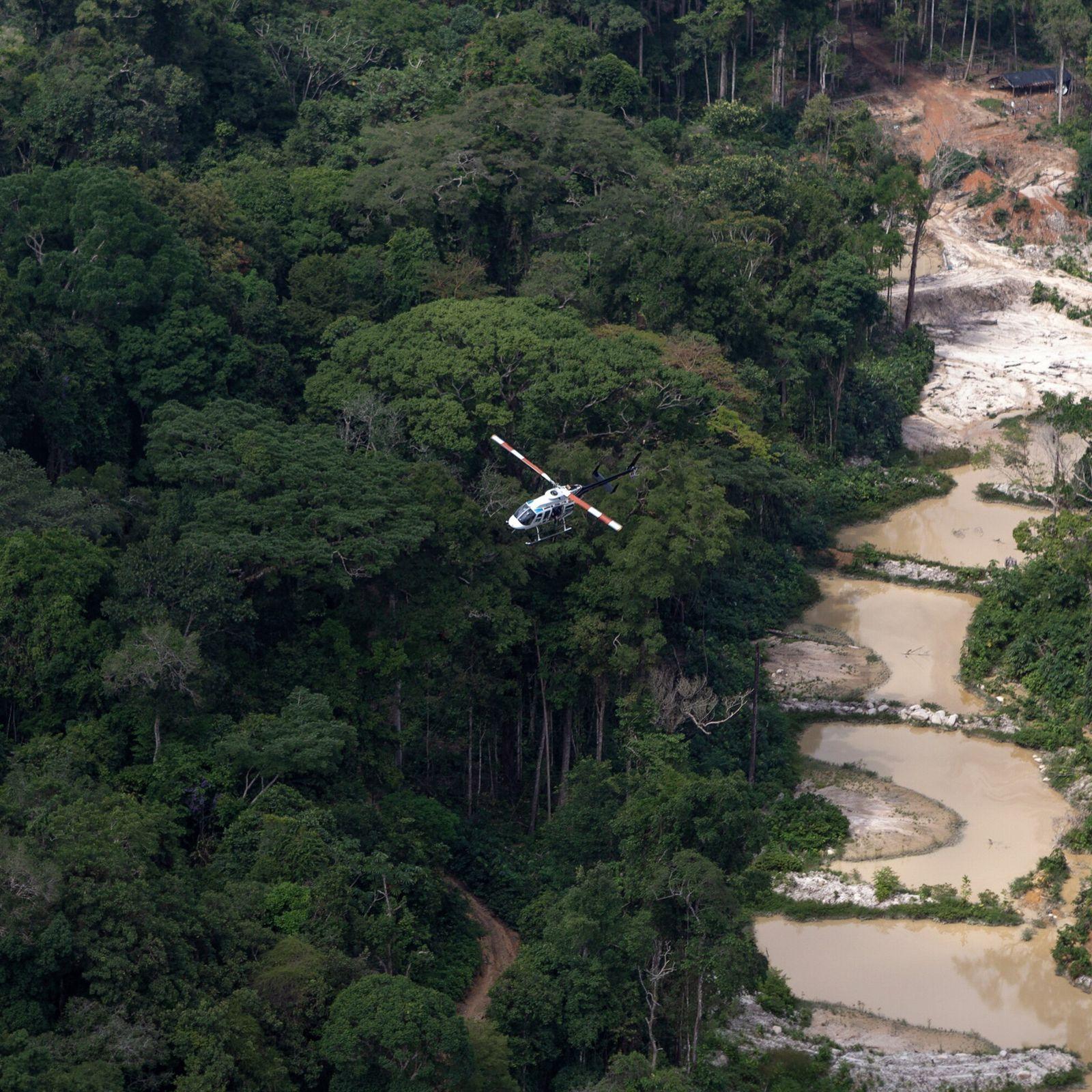 Foto aérea de helicóptero sobrevoando zona de floresta à esquerda e um garimpo à direita