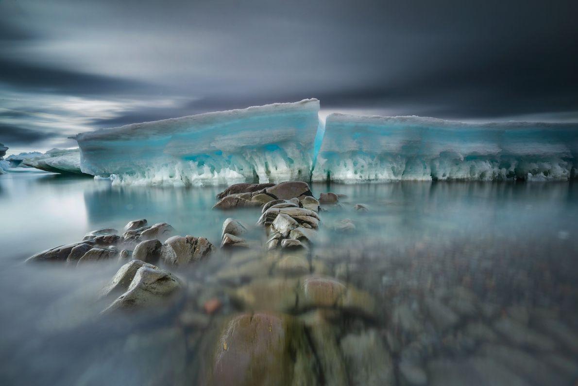 Pedras erodidas pelo mar formam uma passagem até o gelo rompido e encalhado. O gelo é ...