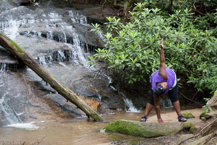 Valerio practices yoga by a waterfall near Georgia's Blackrock Lake.