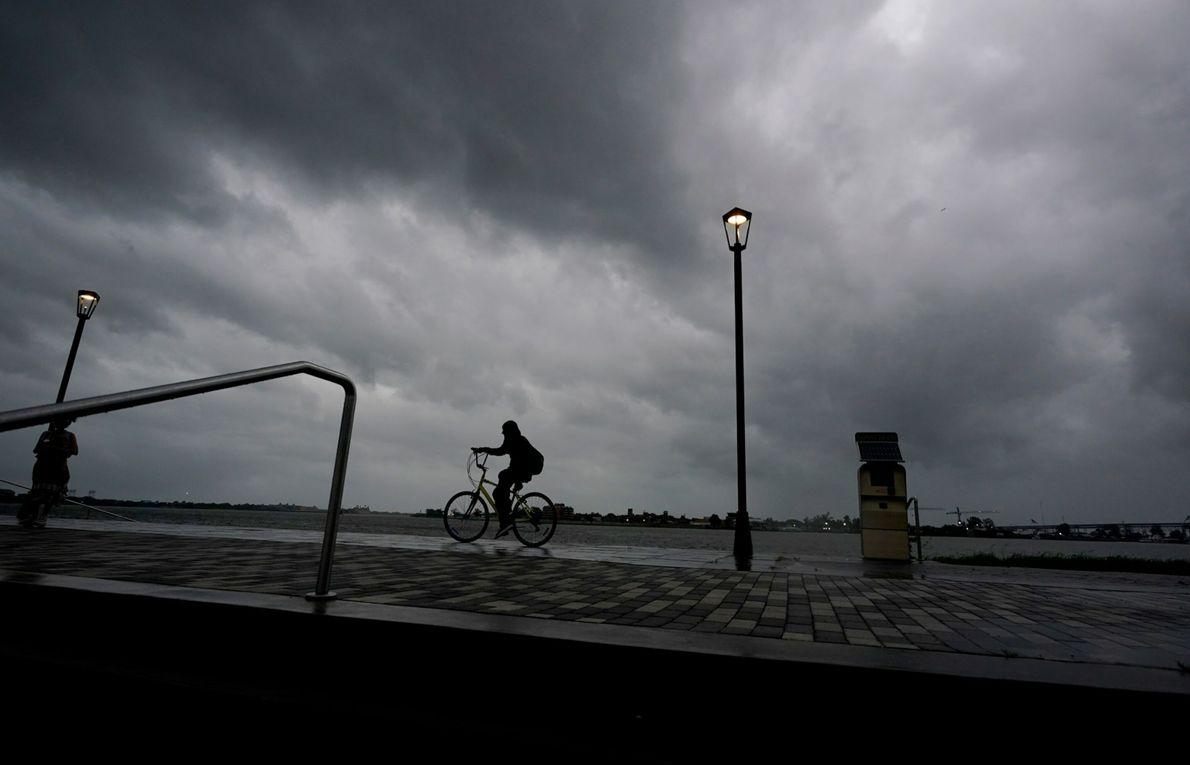 Um homem anda de bicicleta ao longo do rio Mississippi, perto do French Quarter, ao amanhecer, ...