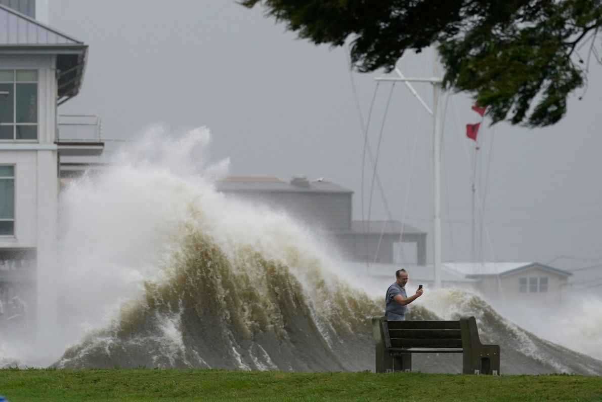 Um homem usa seu celular para tirar fotos das imponentes ondas ao longo da costa do ...