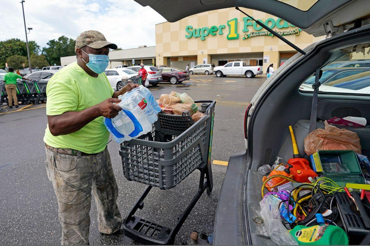 Terry Shelvin guarda um fardo de garrafas de água e alguns alimentos em seu carro, em ...