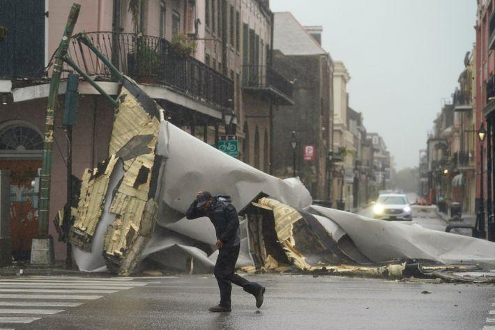 Um homem passa por um pedaço do telhado que foi arrancado de um prédio pelo furacão ...