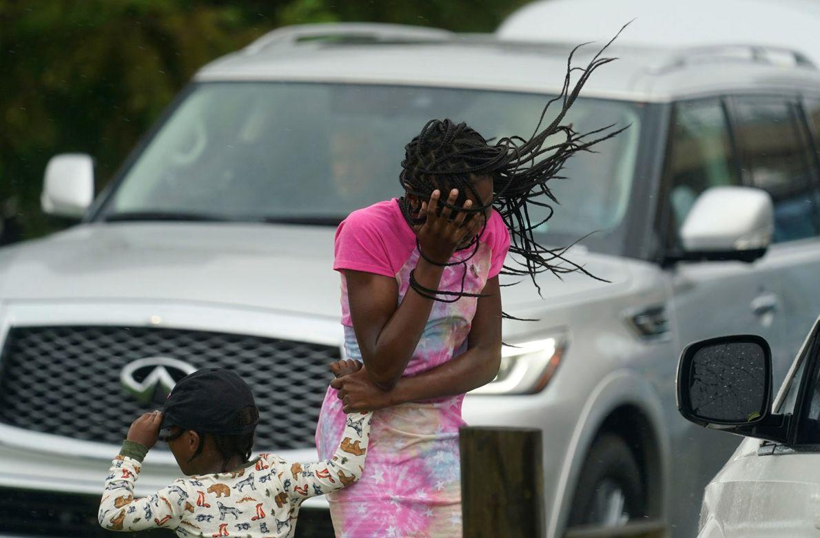 Uma jovem protege seu rosto do vento e da chuva causados pelo furacão Ida, em Nova ...