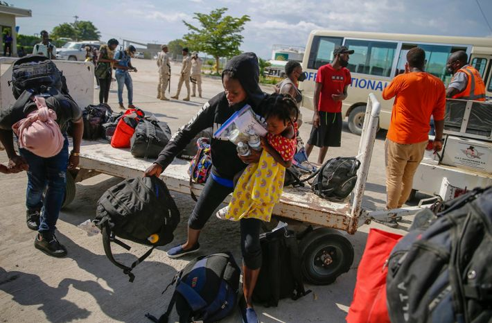 Pessoas que foram deportadas pegam as malas em um carrinho