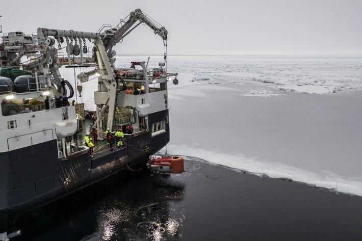 O veículo Nereid Under Ice, de cor laranja brilhante, é movimentado pelo Kronprins Haakon nas águas ...