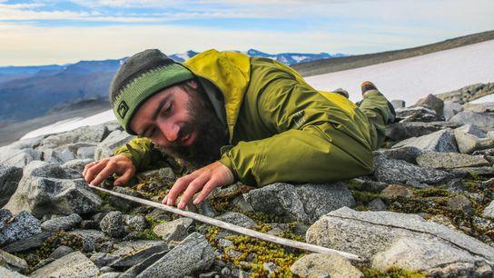 Um pesquisador examina a haste de madeira de uma flecha que emergiu da camada de gelo ...