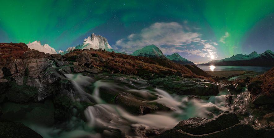Uma aurora boreal brilha no céu noturno próximo ao Fiorde Tasermiut. O fiorde possui montanhas conhecidas, incluindo Ulamertorsuaq (ao centro), cujo pico mais alto tem 1,8 mil metros. Chu fez uma trilha de dois dias até chegar à área isolada.