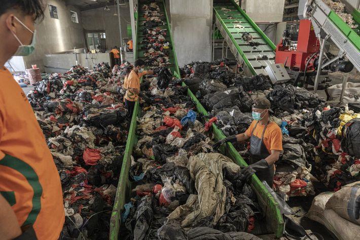 Trabalhadores colocam em esteiras o lixo plástico que será lavado e triturado na unidade de reciclagem ...