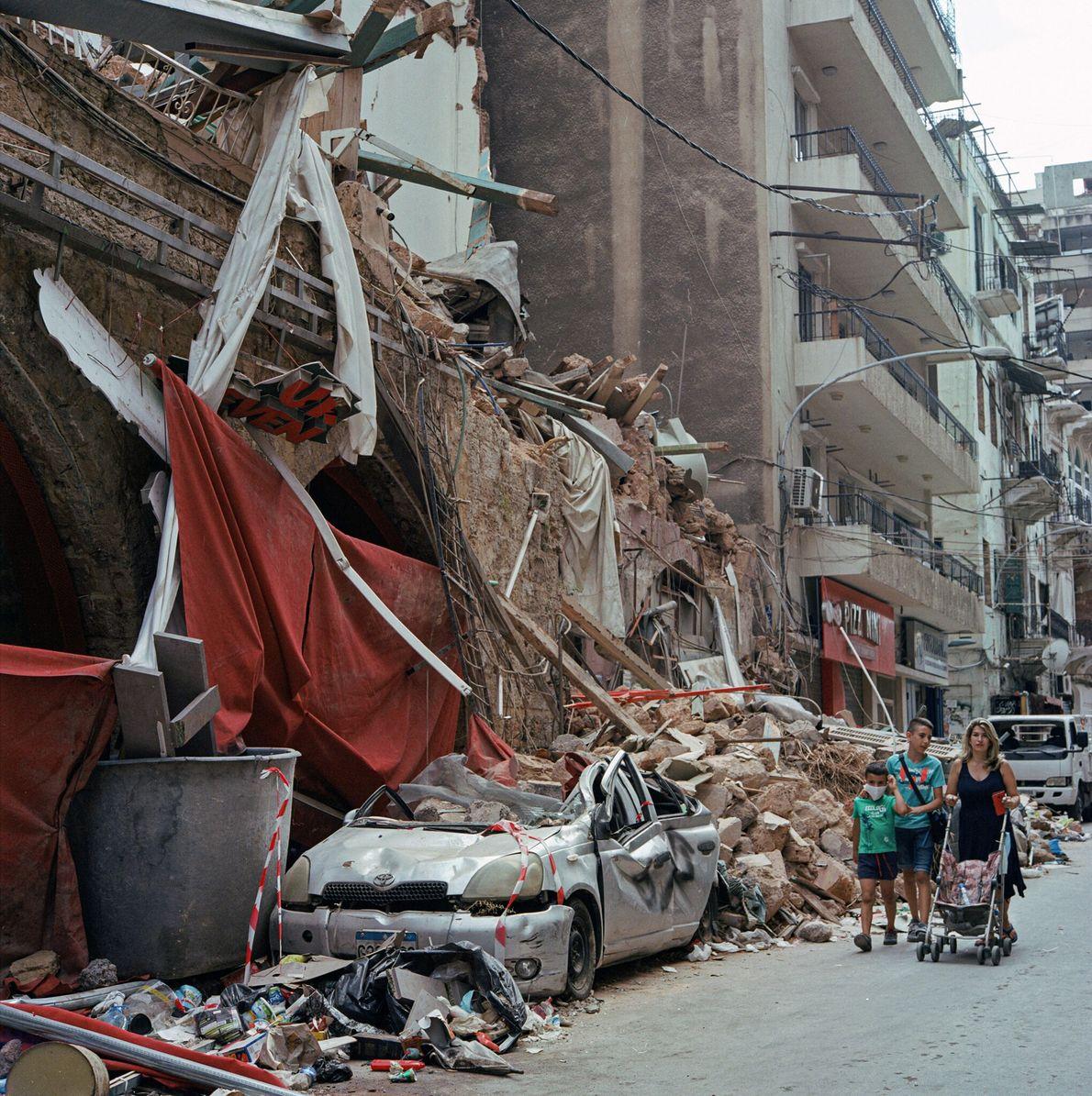 Pedestres passam por prédios em ruínas no bairro de Mar Mikhael, em Beirute, no Líbano, depois ...