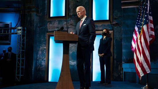 O presidente eleito Joe Biden discursa, observado ao fundo pela vice-presidente eleita Kamala Harris, no teatro ...