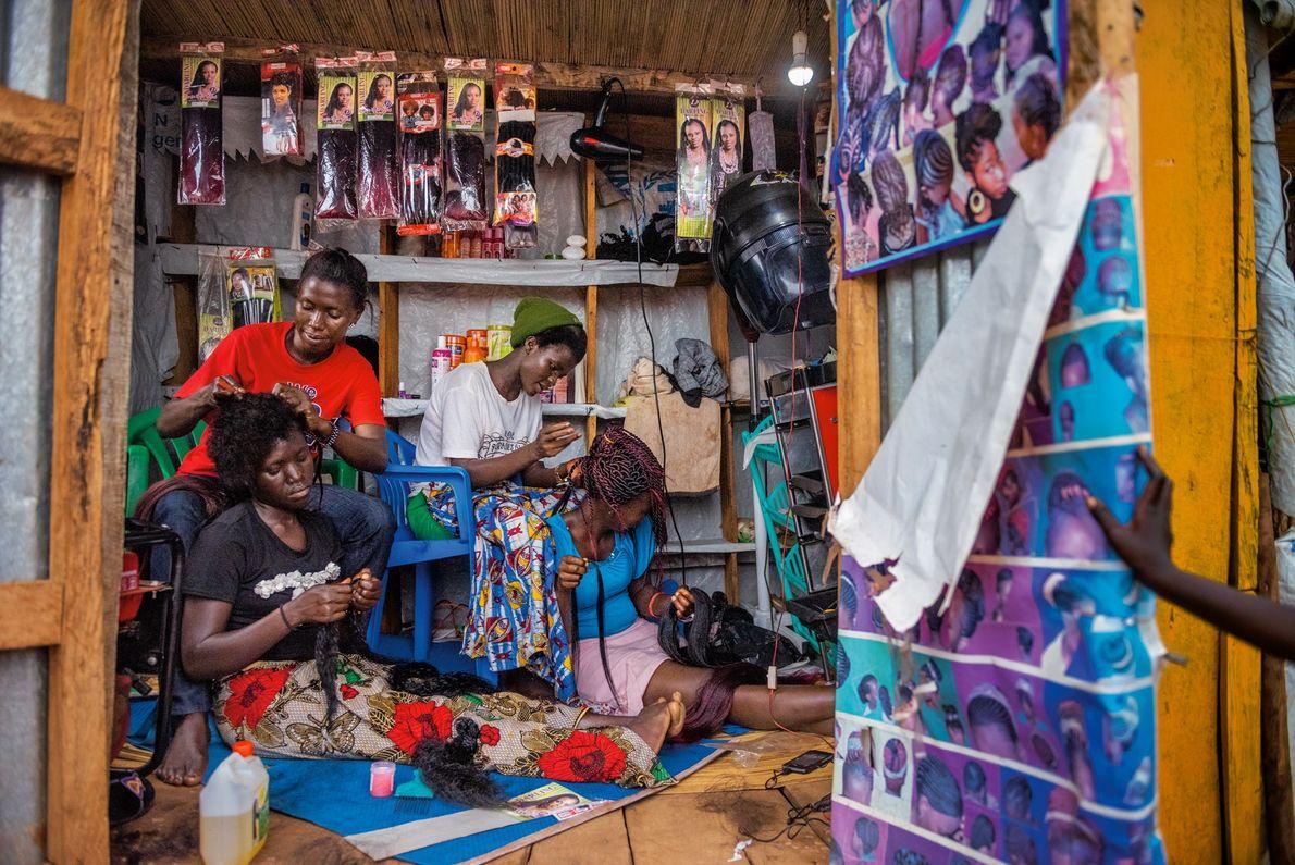 Knight Mai (à esquerda) e Florence Stima (à direita), sul-sudaneses, trabalham em um salão no acampamento ...