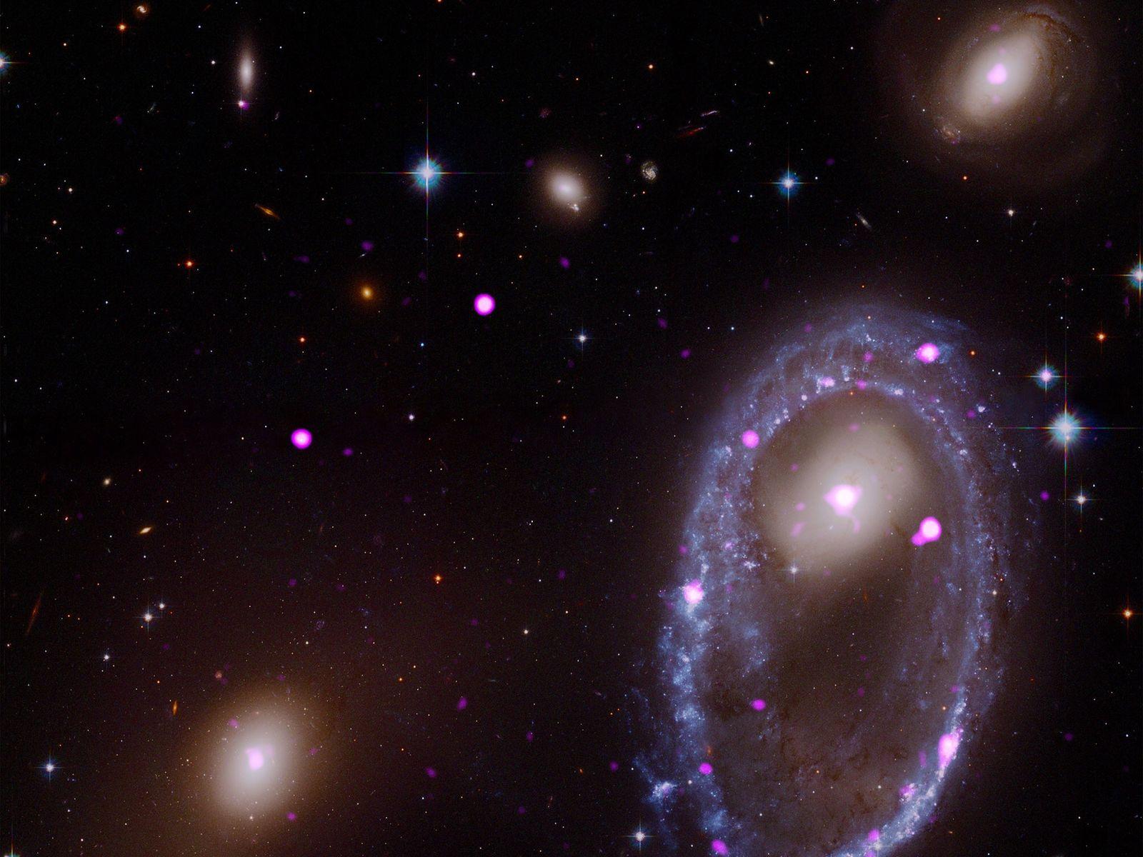 Uma imagem composta dos telescópios espaciais Hubble e Chandra mostra a galáxia de anel conhecida como ...