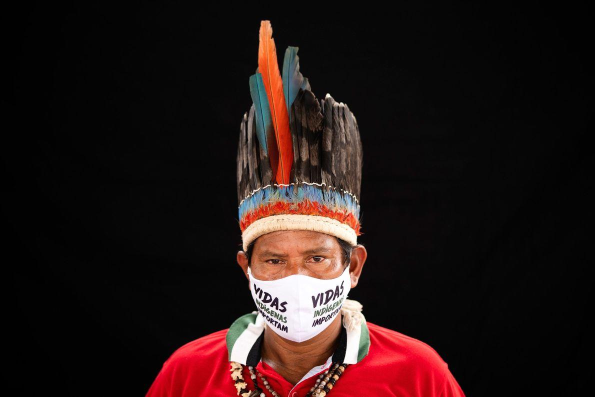 Um líder da comunidade miranha usa cocar tradicional e máscara facial com a frase Vidas Indígenas Importam. ...