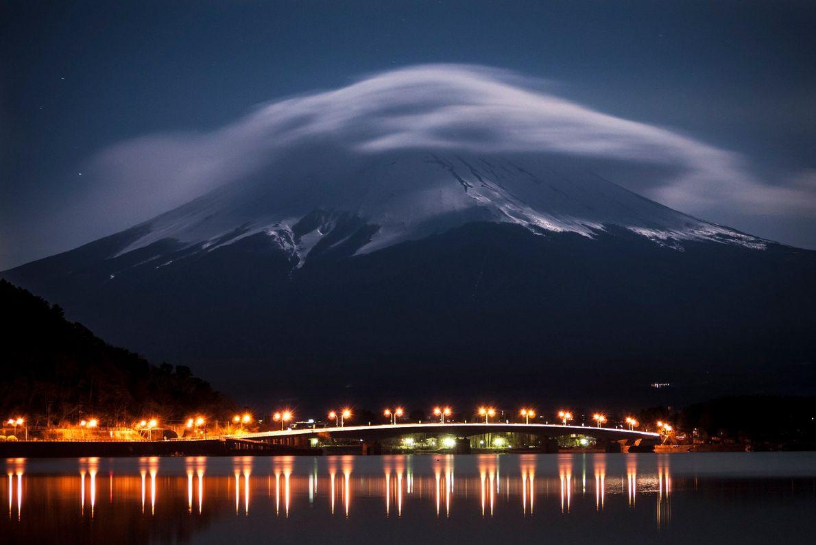 O Monte Fuji brilha na luz do luar enquanto o lago Kawaguchi é iluminado pelas luzes ...