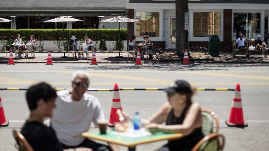 Clientes em mesas ao ar livre em ambos os lados da Newton Lane, em East Hampton, ...