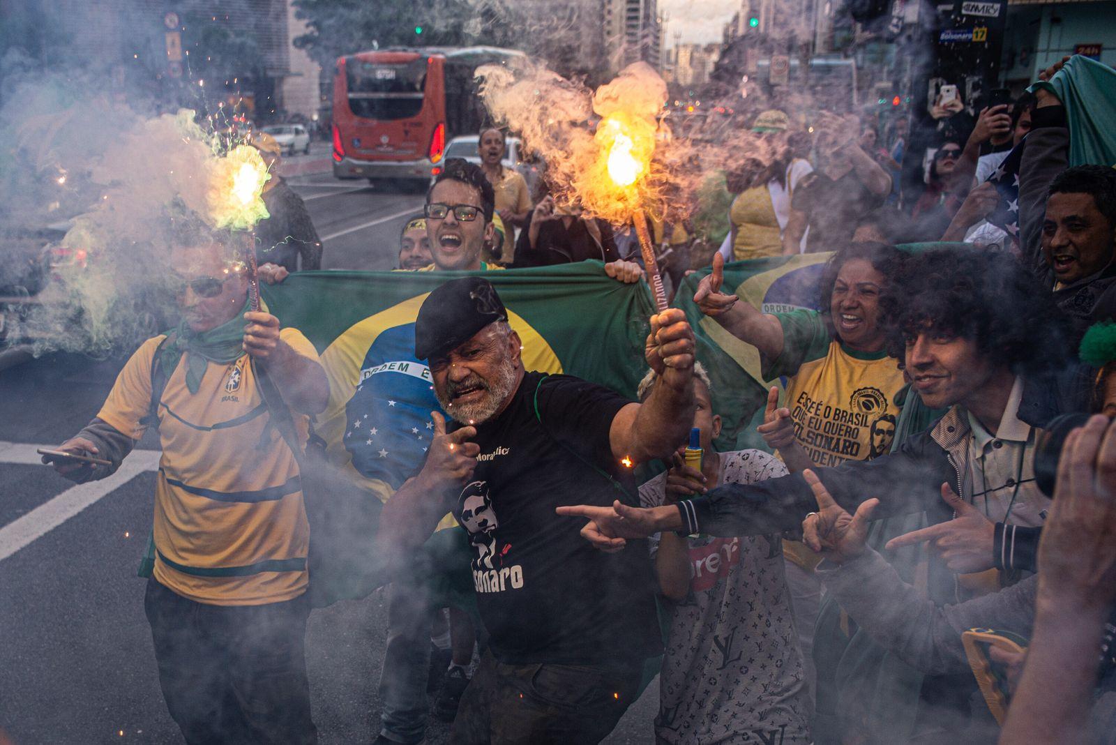 Apoiadores do presidente Jair Bolsonaro fazem gestos simulando armas enquanto comemoram a eleição do mandatário, em outubro de ...