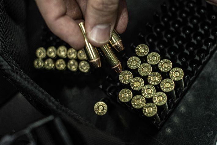Atirador esportivo escolhe munições para utilizar durante a prática em um clube de tiro do interior ...